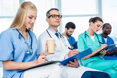 Doctors listening to lecture and writing. Concentrated group of doctors listening to lecture and writing in clipboards Royalty Free Stock Photos