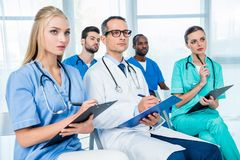 Doctors listening to lecture and writing. Concentrated group of doctors listening to lecture and writing in clipboards Stock Images