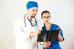 Doctors look at the X-ray, they see the problem and discuss it. White background royalty free stock photo