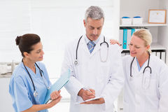 Doctors looking at clipboard Stock Photo