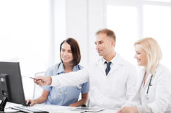 Doctors looking at computer on meeting Stock Image