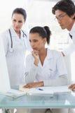 Doctors looking at a computer monitor Stock Image