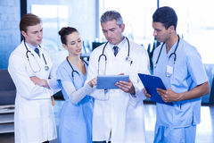 Doctors looking in digital tablet. Portrait of doctors showing medical reports in hospital Stock Photography