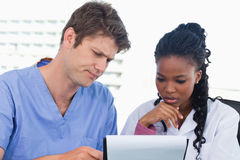 Doctors looking at a document Royalty Free Stock Photos