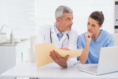 Doctors looking at files. In medical office Royalty Free Stock Image