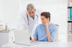 Doctors looking at laptop Stock Photo