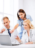 Doctors looking at laptop on meeting. Healthcare, medical and technology - group of doctors looking at laptop on meeting Royalty Free Stock Photography
