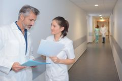 Doctors looking at notes in hospital corridor royalty free stock photography