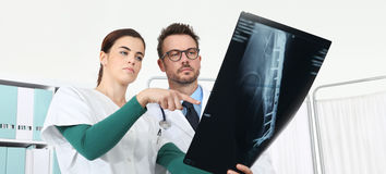 Doctors looking at x-ray in medical office. Pointing with finger stock image
