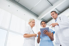 Doctors looking together at tablet Stock Images