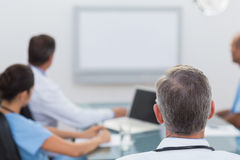 Doctors looking at white board. In meeting Stock Photography