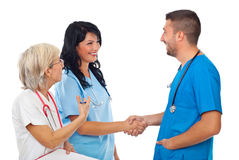 Doctors make acquaintance. Two smiling doctors make acquaintance while the senior woman presenting young woman to man isolated on white background,check also stock images