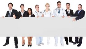 Doctors and managers presenting empty banner. Group of doctors and managers presenting empty banner. Isolated on white Royalty Free Stock Photo