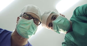 Doctors in masks and medical uniforms looks down at patient. 4K Close-up. Doctors in masks and medical uniforms looks down at patient. Surgeons shake their stock footage