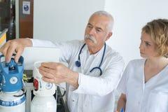 Doctors measuring oxygen flow bottles. Doctor royalty free stock photos