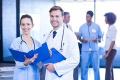 Doctors with medical report looking at camera and smiling. In hospital Royalty Free Stock Images