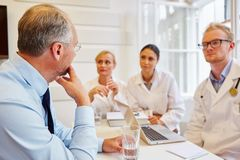 Doctors and medical specialist with patient. In consultation giving him advice Royalty Free Stock Photos