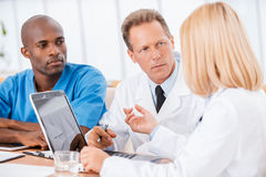 Doctors at the meeting. Three confident doctors discussing something while women using computer and gesturing Royalty Free Stock Photo