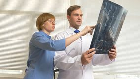 Doctors, a man and a woman analyze the results of MRI , x-ray images. the results of magnetic resonance therapy on film. Doctors, a men and a women analyze the stock photos