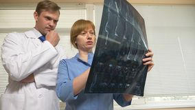 Doctors, a man and a woman analyze the results of MRI , x-ray images. the results of magnetic resonance therapy on film. Doctors, a men and a women analyze the stock image