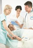 Doctors and nurse examining patient. Doctors and nurse examining old patient in hospital, nurse measuring blood pressure, doctor taking notes royalty free stock photos