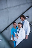 Doctors and nurse holding medical reports standing on stairs. In hospital Stock Photo
