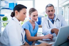 Doctors and nurse looking at laptop Royalty Free Stock Photography