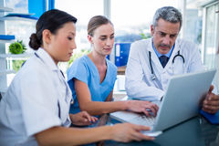 Doctors and nurse looking at laptop Stock Photo