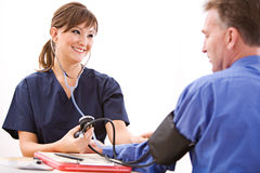 Doctors: Nurse Taking Blood Pressure Stock Image