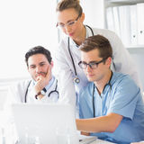 Doctors and nurse working on laptop Royalty Free Stock Photography