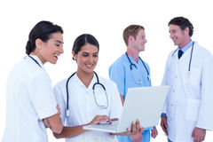 Doctors and nurses discussing and using laptop. Doctors and nurses discussing and using laptotp on a white background Stock Image