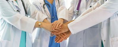 Doctors and nurses in a medical team stacking hands Stock Image