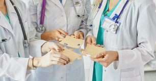 Doctors and nurses in a medical team stacking hands royalty free stock image