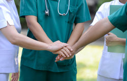 Doctors and nurses in a medical team stacking hands outdoor on t. He green park background volunteer Royalty Free Stock Images