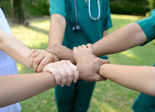 Doctors and nurses in a medical team stacking hands outdoor on t. He green park background volunteer Stock Photo