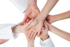 Doctors and nurses stacking hands. Isolated on white Stock Photography
