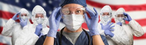 Doctors or Nurses In Hazmat Medical Personal Protective Equipment PPE Against The American Flag Banner