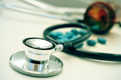 At the doctors office. Closeup of the desk of a doctors office with a stethoscope and a bottle with pills royalty free stock photos