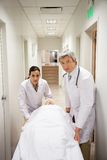 Doctors With Patient In Corridor Stock Photo