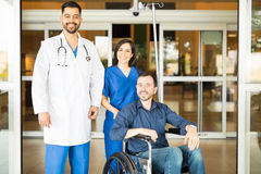 Doctors and patient in hospital entrance Stock Photos
