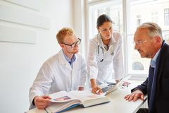 Doctors with patient. Doctors with senior patient in consultation about therapy royalty free stock photos