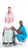 Doctors with a patient in a wheel chair smiling Stock Photos