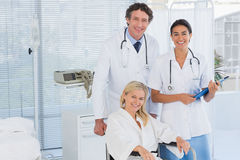 Doctors and patient in wheelchair smiling at camera Stock Image