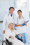 Doctors and patient in wheelchair smiling at camera Royalty Free Stock Photography