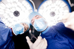 Doctors performing dental surgery. Team of surgeons operating patient under surgery lights in hospital. Doctors performing dental surgery Royalty Free Stock Photos