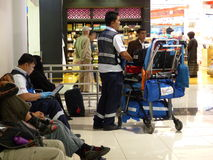 Doctors with portable ambulance equipment in airport Stock Photos
