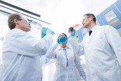 Doctors pretending to drink from test tubes. A team of doctors in lab coats pretending to drink from test tubes in chemical laboratory Stock Photo