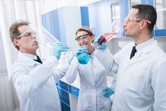 Doctors pretending to drink from test tubes. A team of smiling doctors in lab coats pretending to drink from test tubes in chemical laboratory Royalty Free Stock Photos
