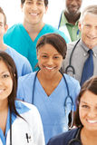 Doctors: Pretty Doctor in Midst of Physician Group Stock Photo