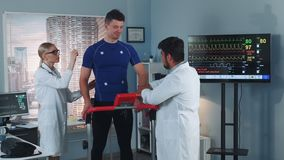 Doctors putting electrodes on sportsmas standing on racetrack. In big modern lab with skyscrapers in the background stock footage